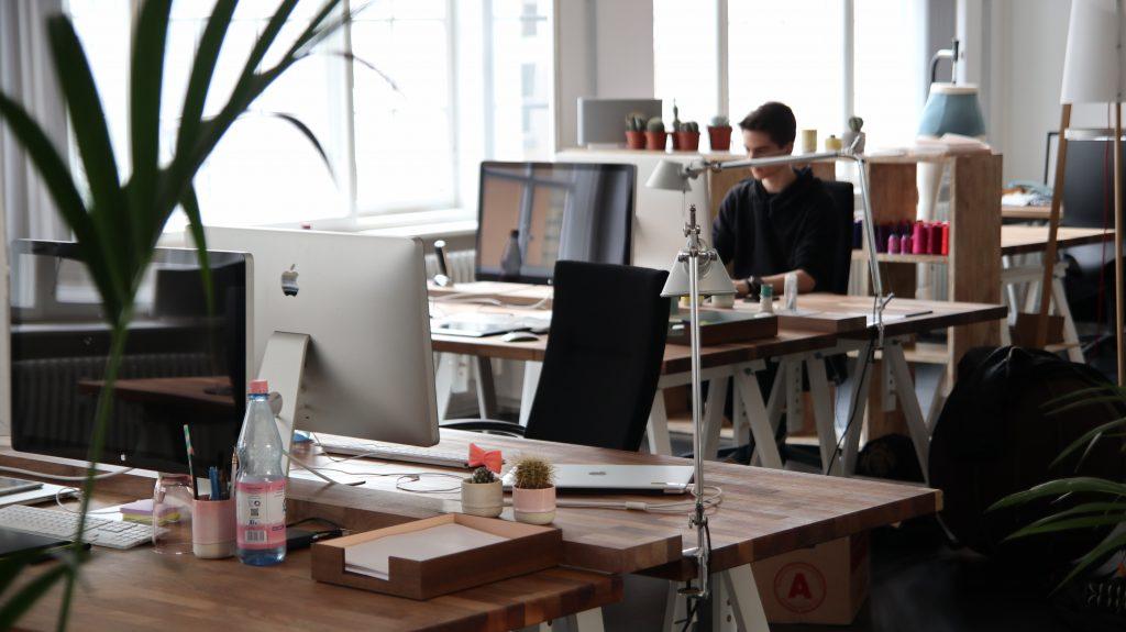 Open space constitué de plusieurs bureaux avec un salarié au second plan