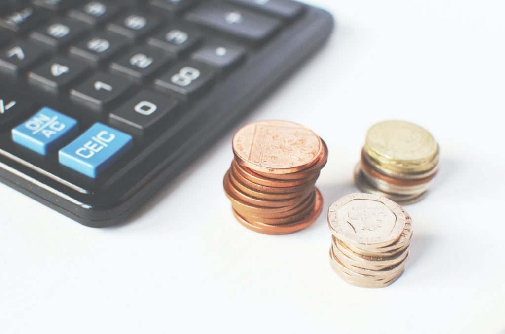 tas de pièces posés à côté d'une calculatrice