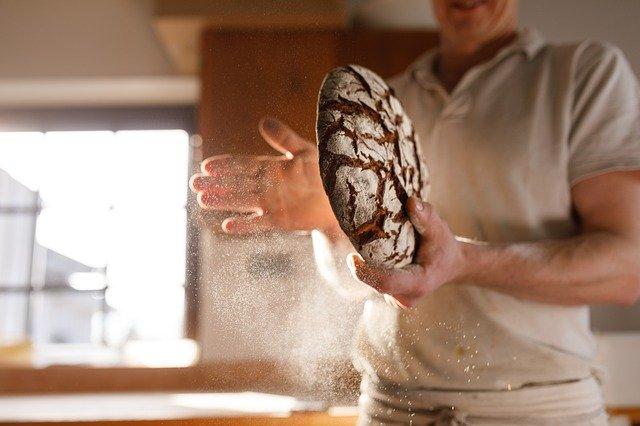 boulanger avec un pain dans les mains